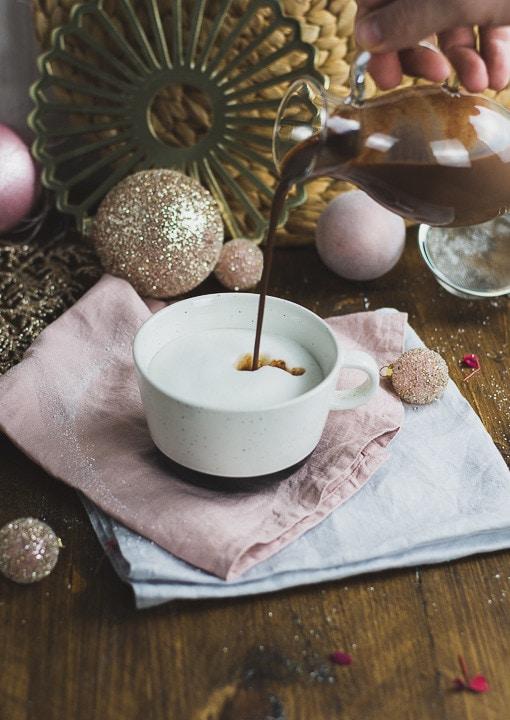Heiße Schokolade wird in eine Tasse mit Milch gegossen