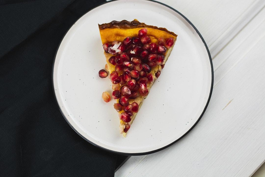 Ein Stück Granatapfel Tarte auf einem weißen Teller mit schwarzen Rand