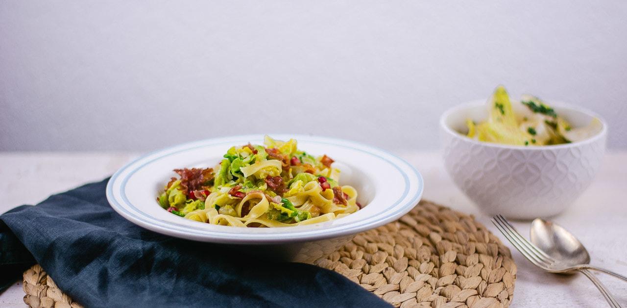 Ein Teller mit Pasta und Rosenkohl. Daneben steht ein Salat und Besteck