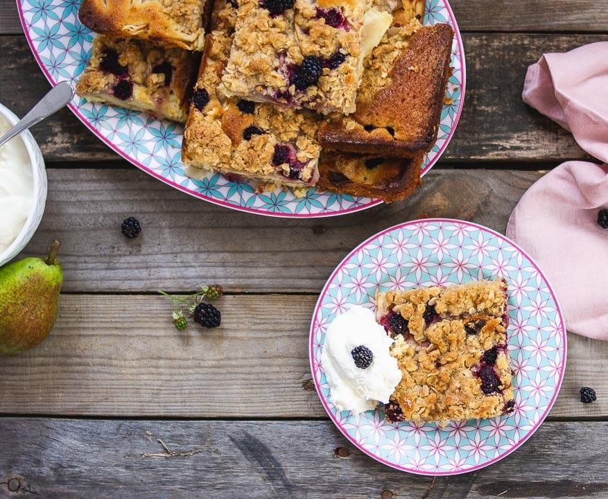 Ein Stück Birnen Streuselkuchen mit einem Sahne auf einem bunten Teller