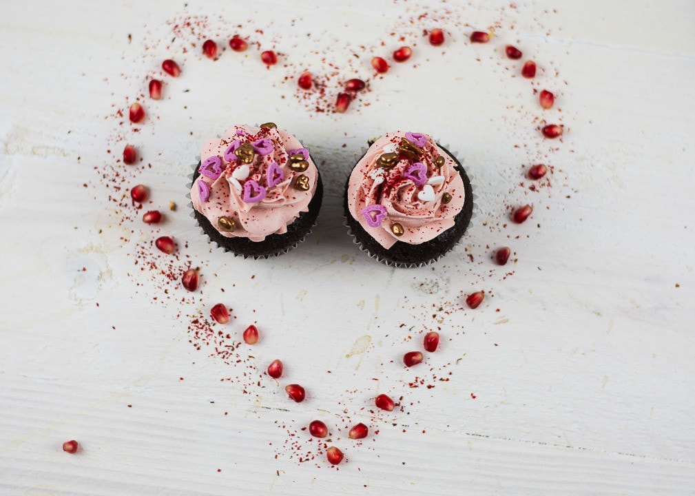 Ein Herz aus Granatäpfel mit zwei Valentinstag Cupcakes