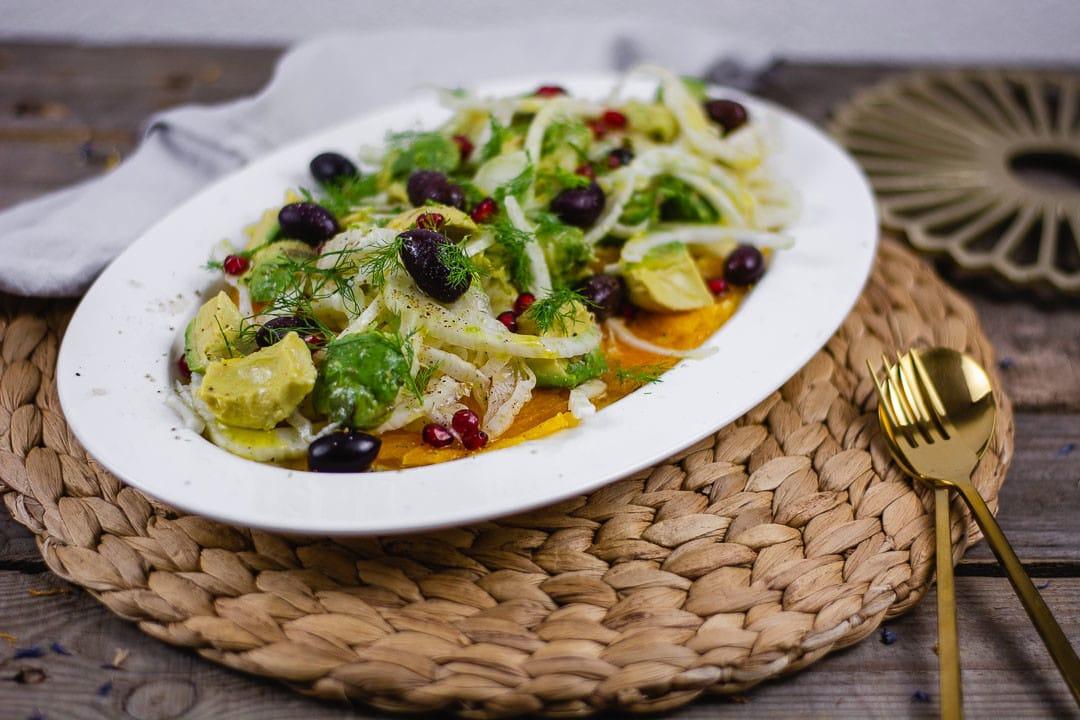Der Fenchel Avocado Salat auf einem weißen Teller. Daneben liegt goldenes Besteck