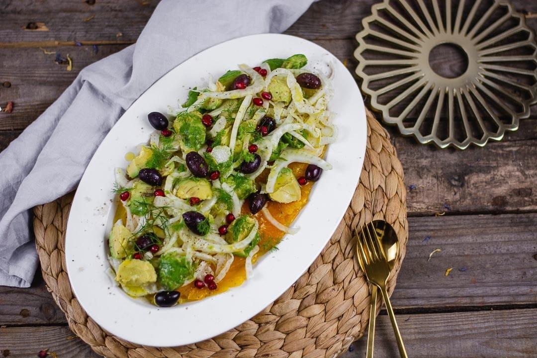 Ein Fenchel Avocado Salat auf Orangen. Daneben liegt ein Löffel und eine Gabel