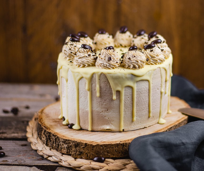 Eine Mokkatorte mit weißer Schokolade auf einem Holzteller