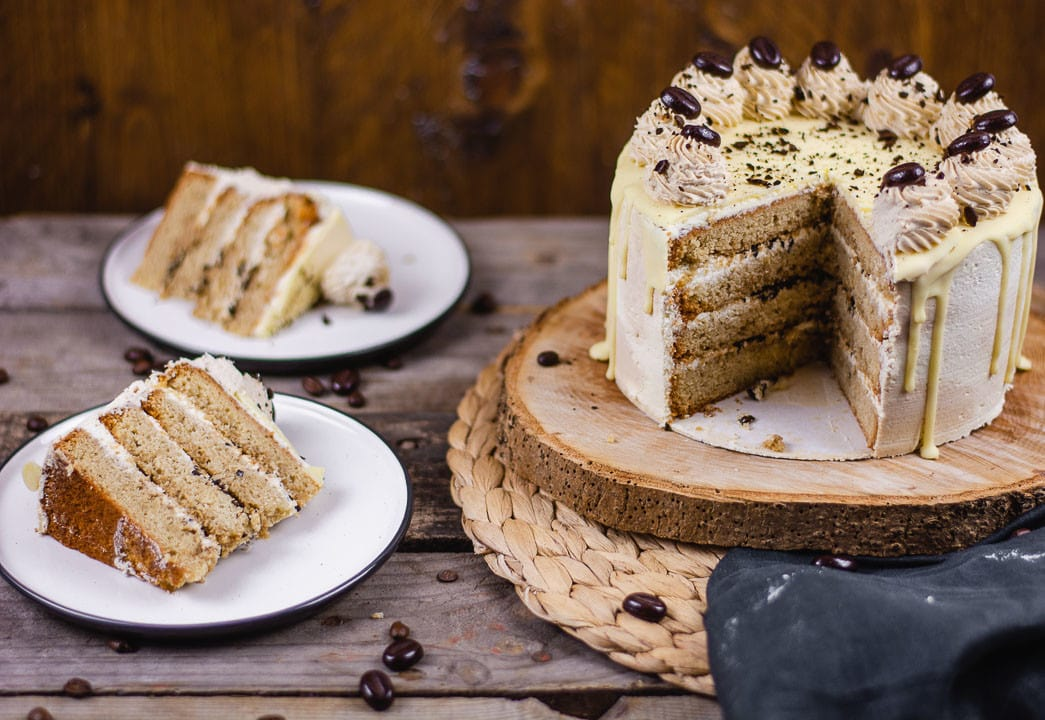 Eine angeschnittene Mokkatorte. Daneben stehen zwei Stücke Kuchen auf einem Teller