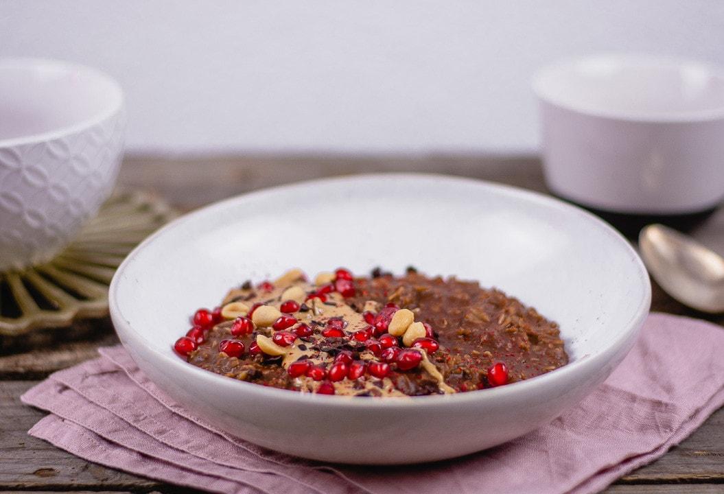 Ein Teller Porridge mit Erdnussbutter. Oben drauf liegen Granatapfelkerne