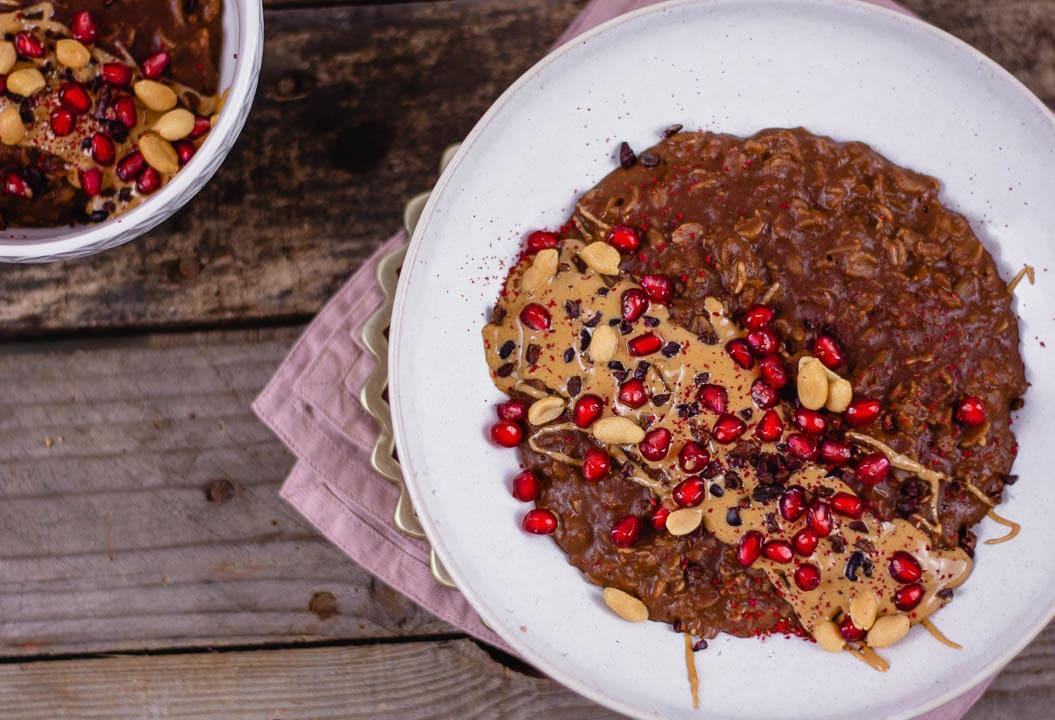 Man sieht Granatapfelkerne und Erdnüsse auf einem Porridge