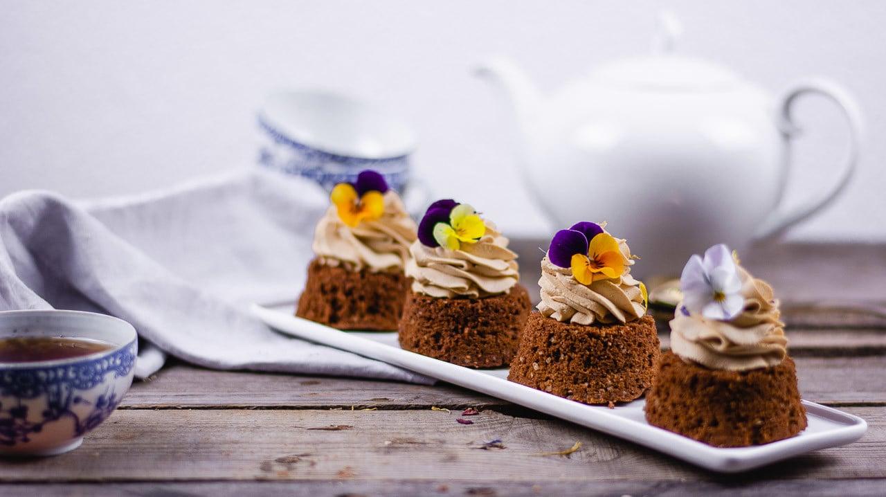Vier Earl Grey Kuchen auf einem Teller. Sie haben eine Creme und sind mit Blüten dekoriert