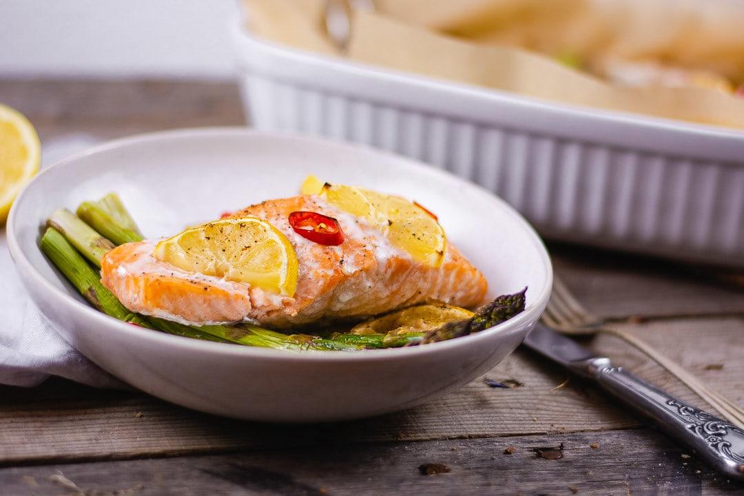 Ein Lachs mit Spargel und Zitronenscheiben auf einem Teller
