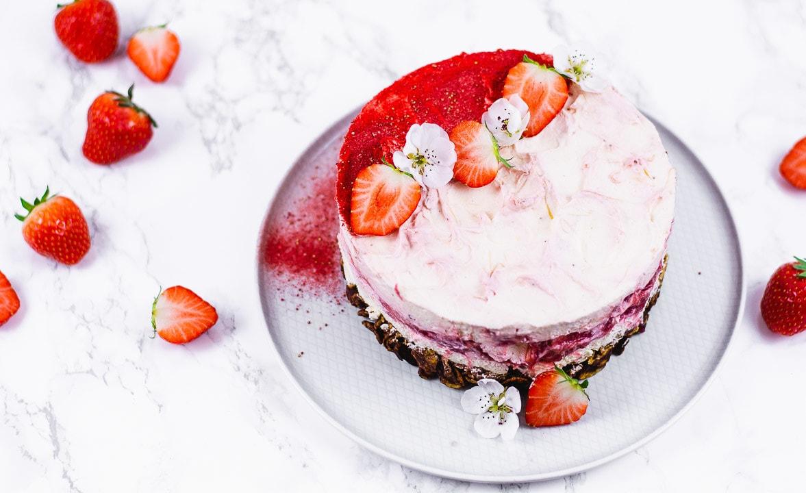 Der no bake Erdbeerkuchen ist mit Erdbeeren und Erdbeerpulver dekoriert