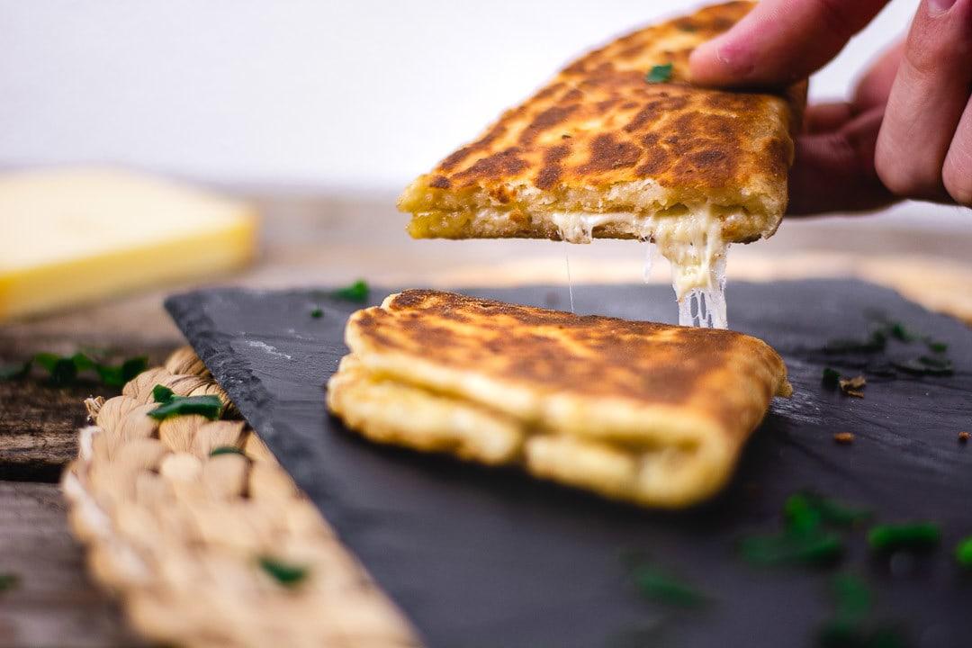 Ein Käse Naan wir mit der Hand hochgehoben