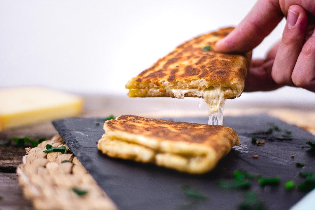 Das Käse Naan wird hochgehoben. Es zieht einen Käsefaden