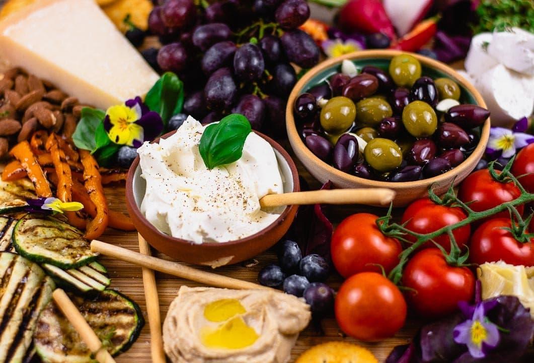 Frischkäse, Oliven, Tomaten, Hummus und gegrilltes Gemüse in der Nahaufnahme