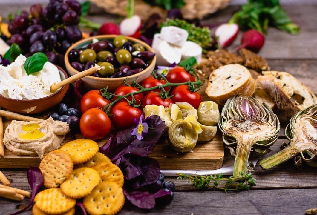 Artischocken, Brot und Hummus liegen an der Seite der Antipasti Platte
