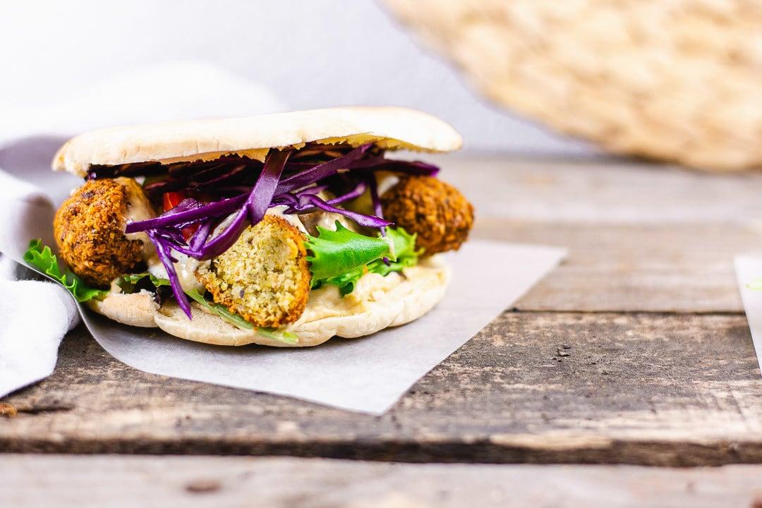 Ein Sandwich mit Falafel, Blaukraut, Hummus und anderem Gemüse