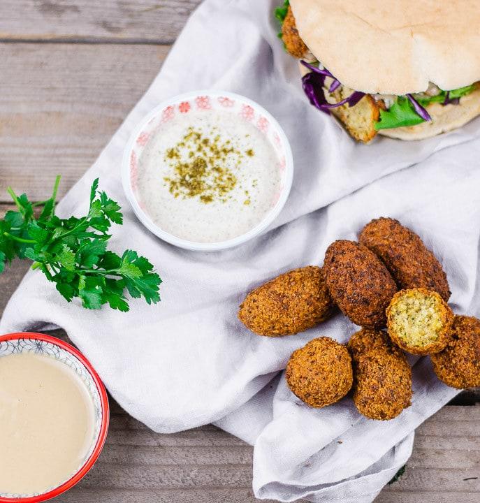 Falafel und Hummus neben einem Falafelsandwich