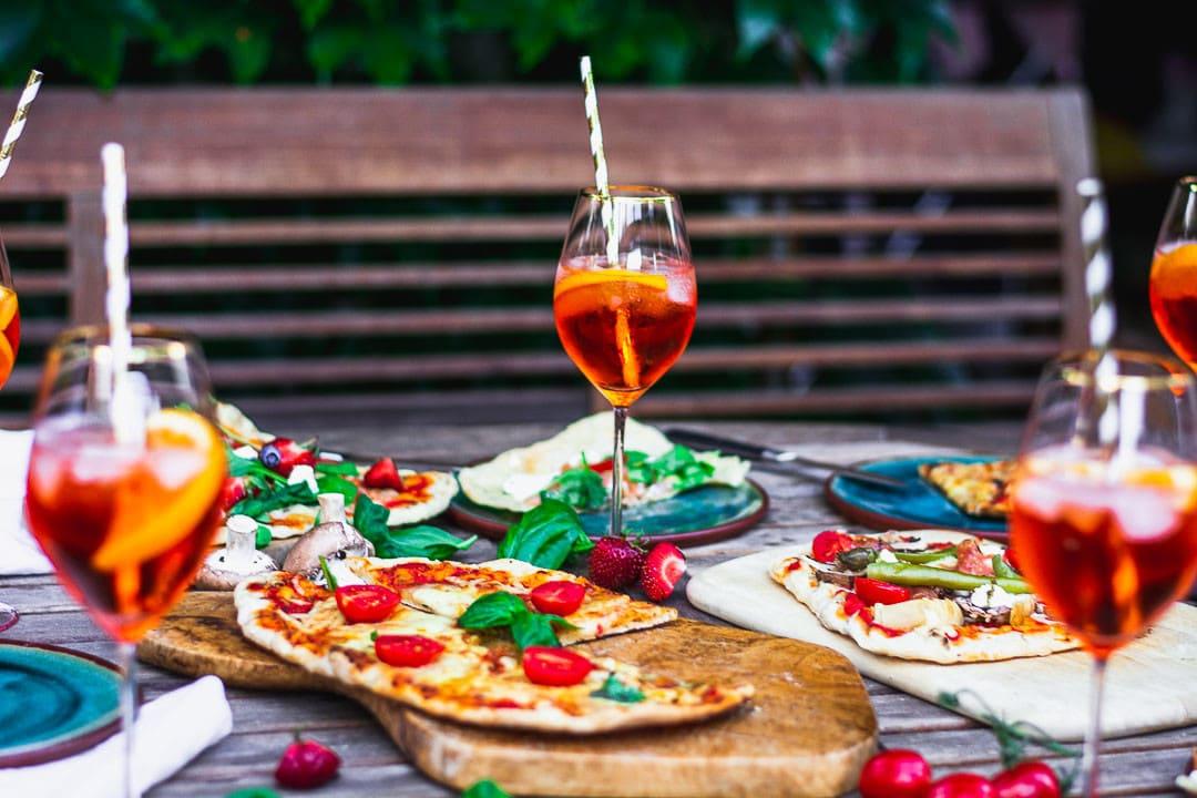 Gegrillte Pizza und Aperitifs auf einem Gartentisch