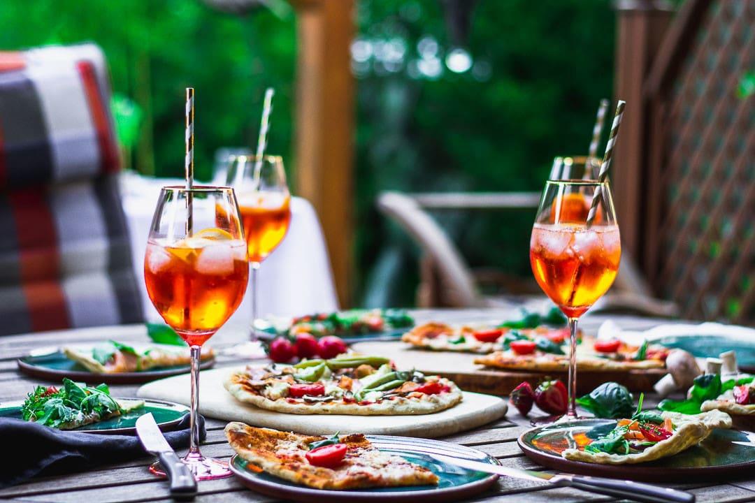 Ein gedeckter Holztisch mit gegrillter Pizza und Aperitifs