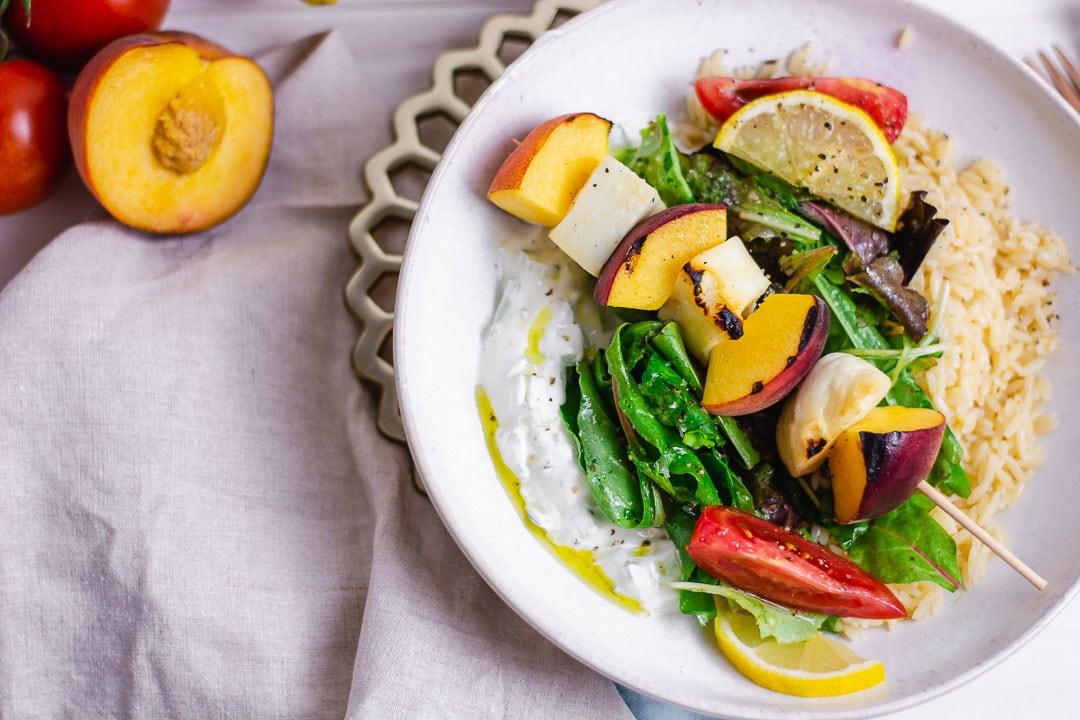 Eine Bowl mit Pfirsich, Halloumi und Salat