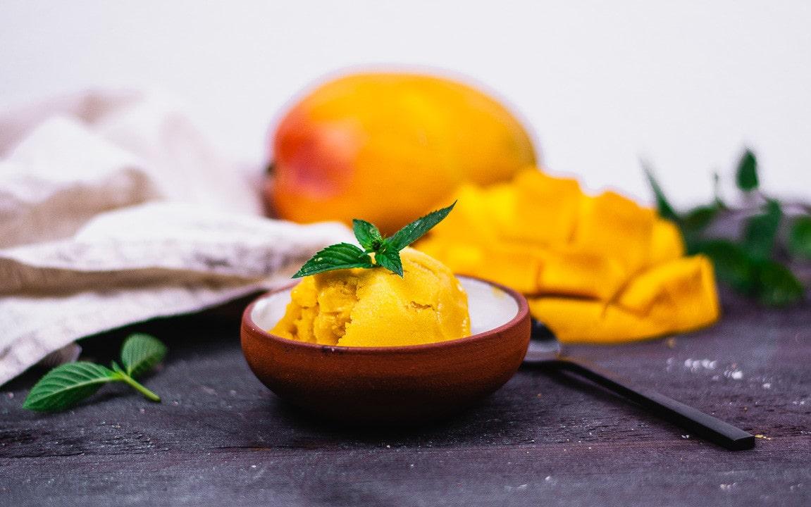 Ein braunes Gefäß aus Ton mit einer Kugel Mango Sorbet
