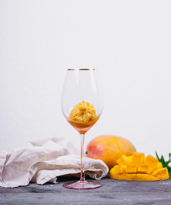 Ein Glas mit einer Kugel Mango Sorbet