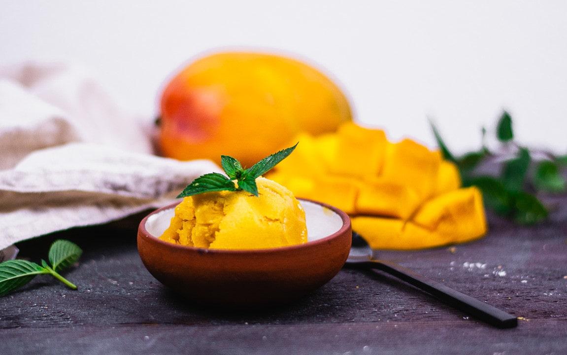 Eine Kugel Mango Sorbet. Im Hintergrund liegt eine Mango