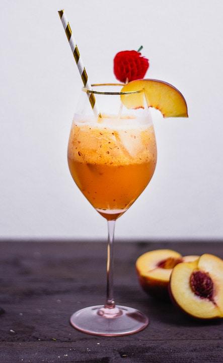 Ein Cocktail mit einem Stück Pfirsich und einem Strohhalm