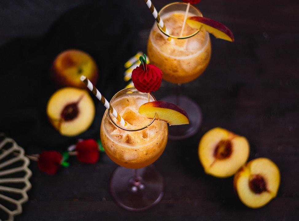 Zwei Cocktails mit Pfirsichstückchen und Eiswürfel von oben