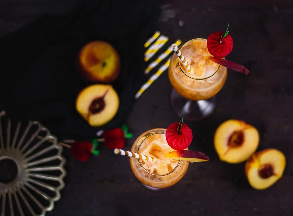 Zwei Pfirsich Cocktails auf einem schwarzen Tisch mit Pfirsichen als Deko