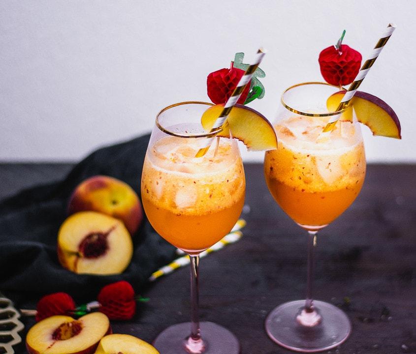 Zwei Bourbon Pfirsich Cocktail mit Pfirsich Dekoration auf einem schwarzen Tisch