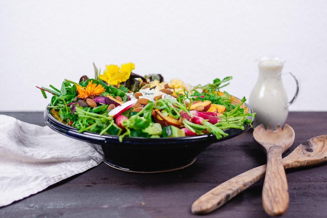 Ein bunt gemischter Salat mit Dressing und Salatbesteck