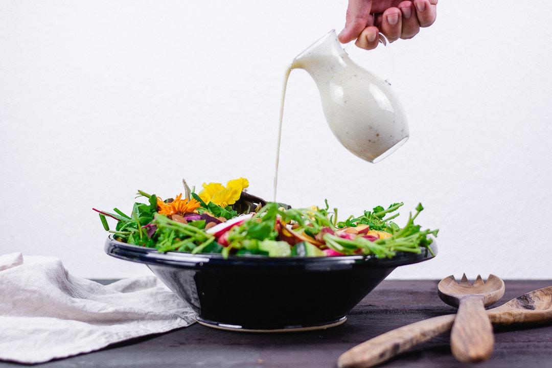 Eine Hand gießt Salatdressing auf den Salat
