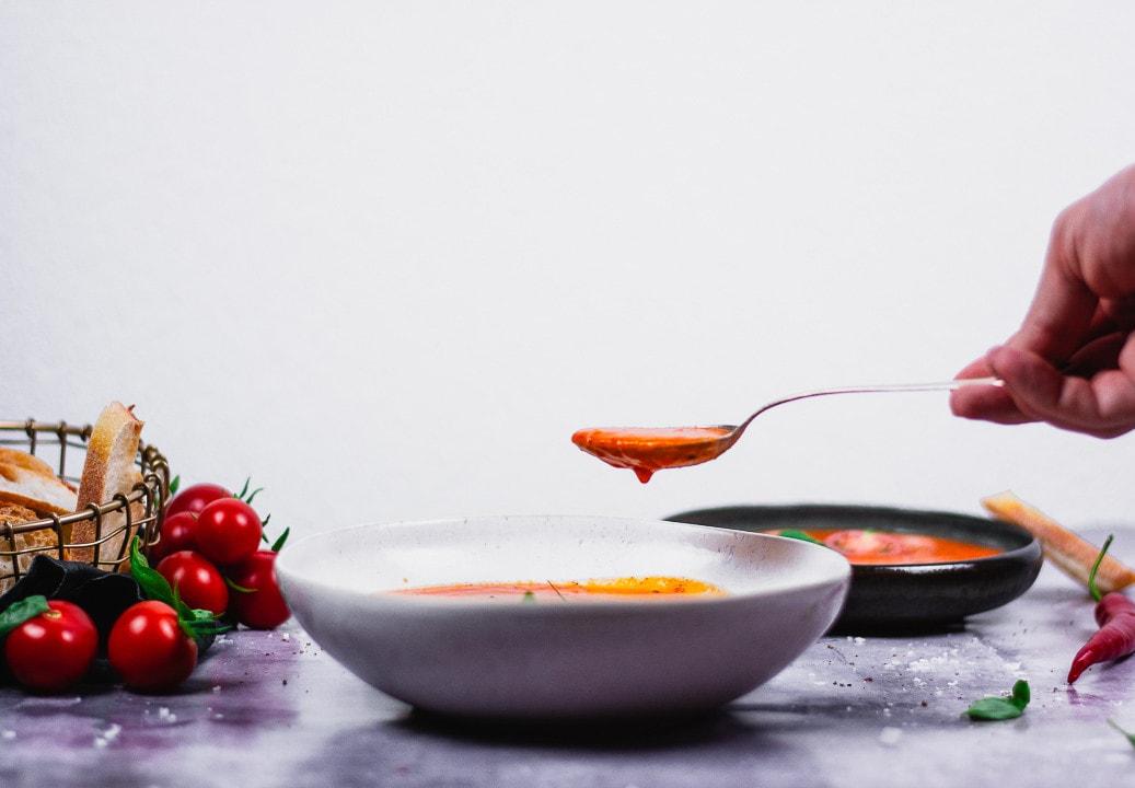 Ein Löffel Tomatensuppe mit gerösteten Tomaten wird hochgehoben