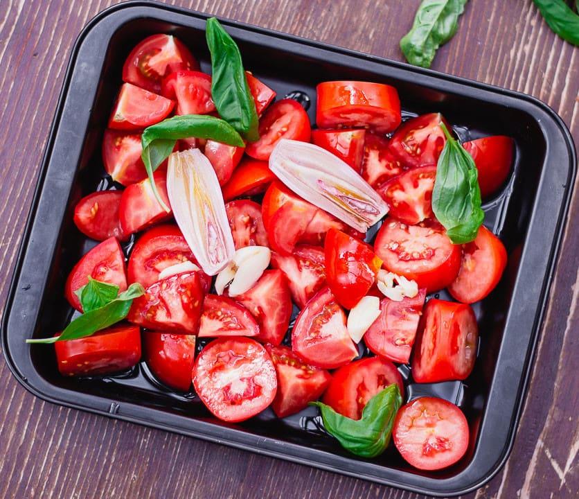 Ein Blech voller Tomaten, Zwiebeln, Knoblauch und Basilikum