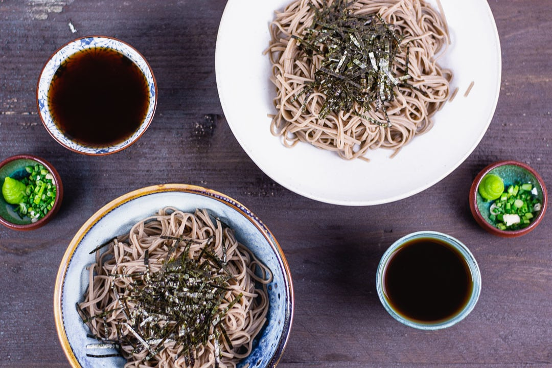 Zwei Teller mit Soba Nudeln. Daneben stehen Wasabi und eine schwarze Soba Sauce