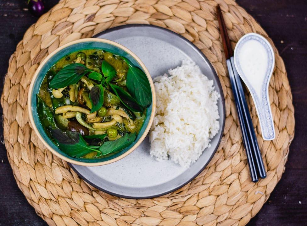 Grünes Thai Curry auf einem Teller. Daneben liegen Stäbchen und ein asiatischer Suppenlöffel