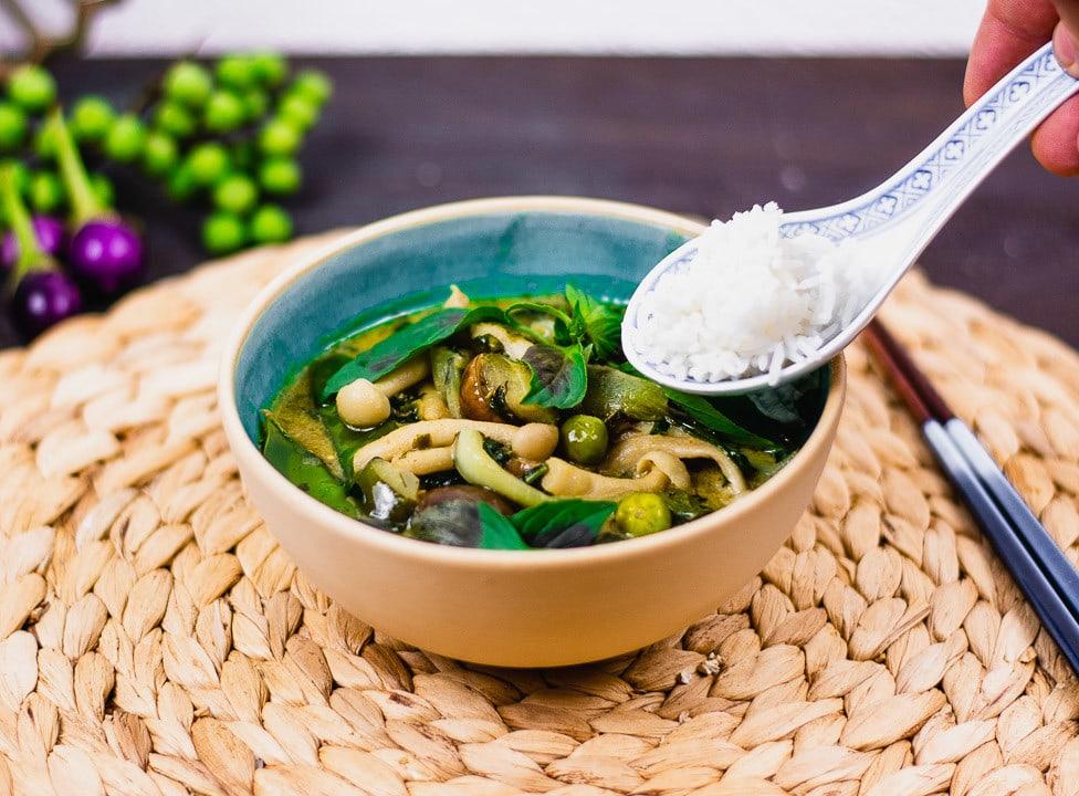 Ein Löffel reis über einer Schüssel mit Thai Curry