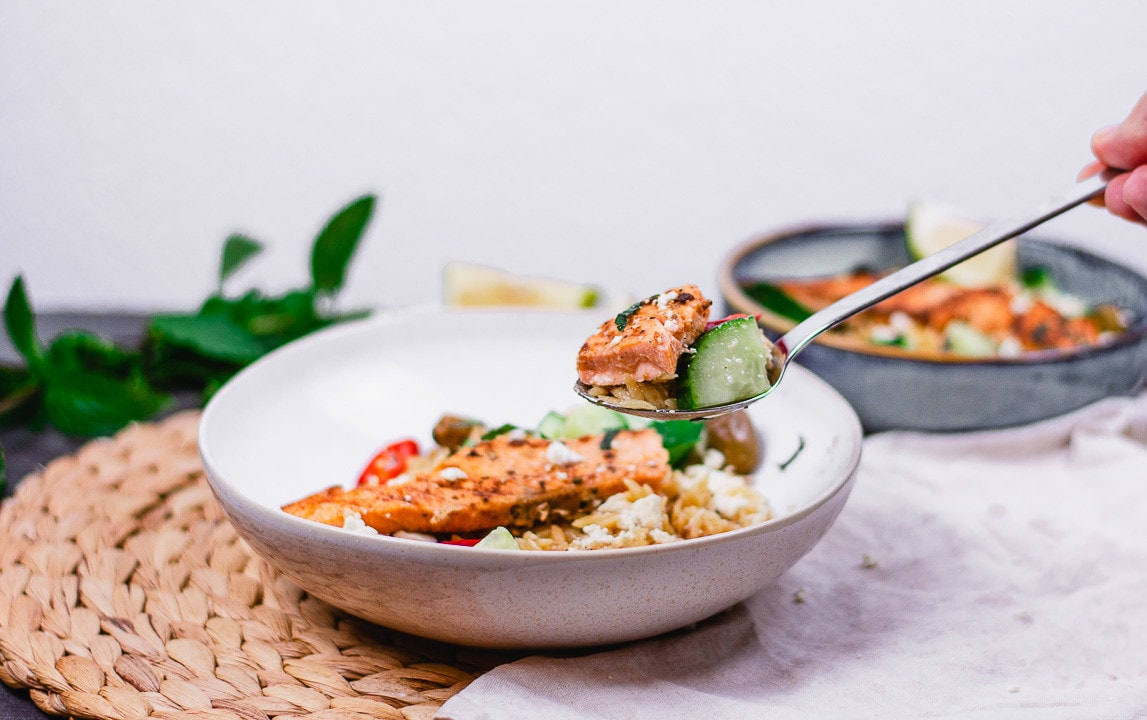 Ein Löffel mit Lachs, Reis und einem Stück Gurke