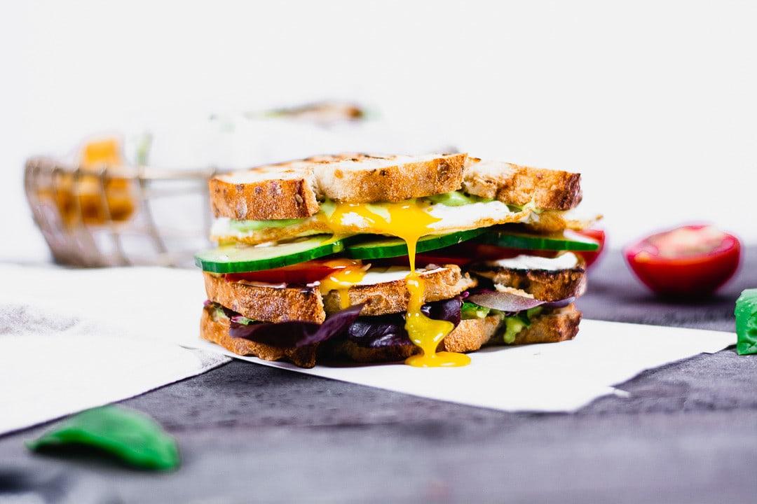 Ein Sandwich, dass auf Backpapier liegt. Käse fliesst an der Seite herunter