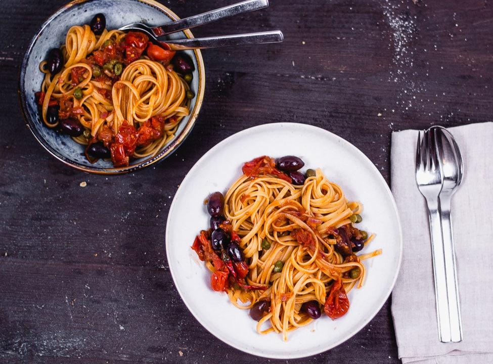 Zwei Teller Spaghetti Puttanesca von oben auf einem schwarzen Tisch