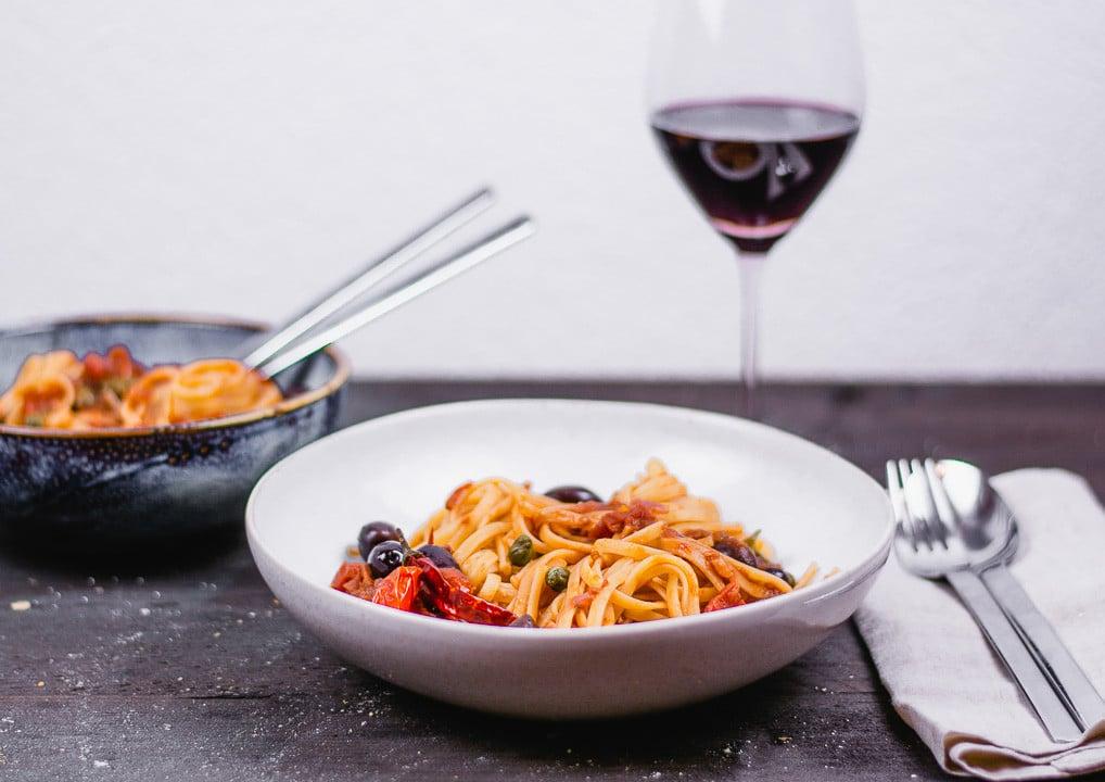 Ein Teller Spaghetti Puttanesca mit einem Glas Rotwein im Hintergrund