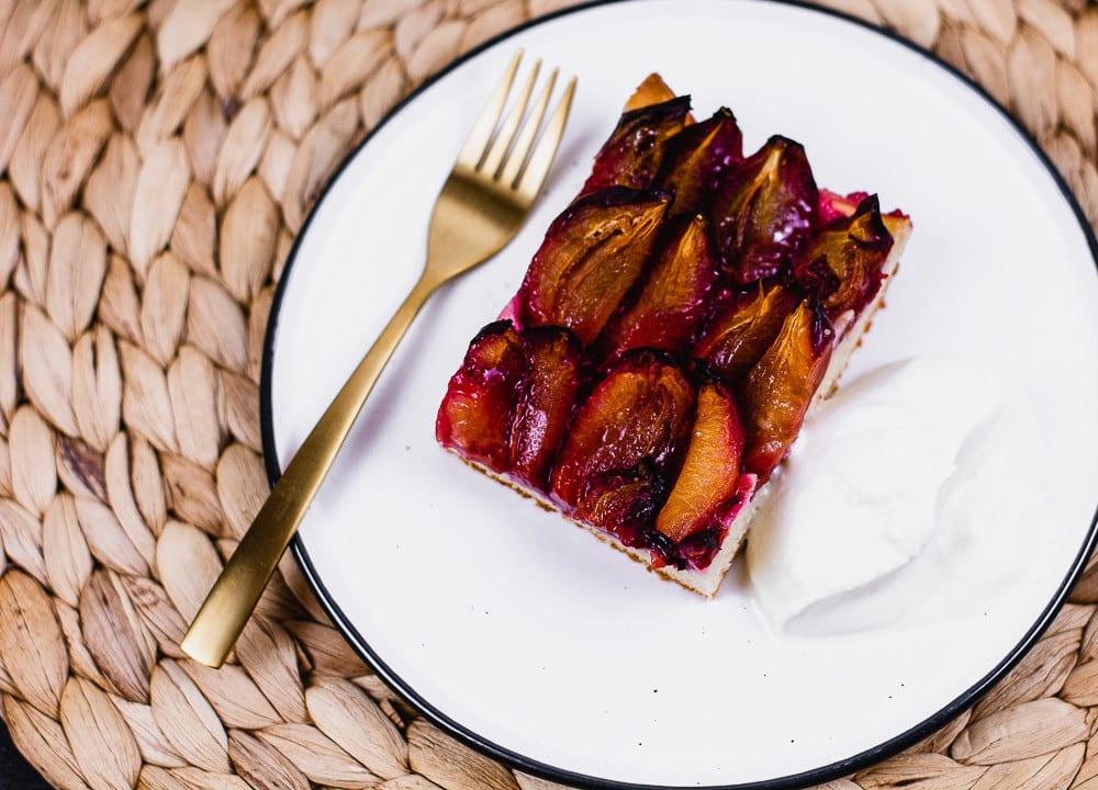 Ein saftiger Zwetschgenkuchen auf einem Teller mit goldener Gabel