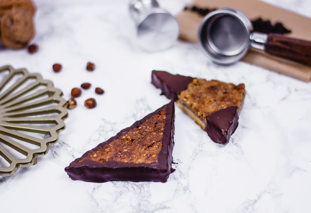 Schokoladige Nussecken liegen auf dem Tisch. Sie sehen aus wie vom Bäcker