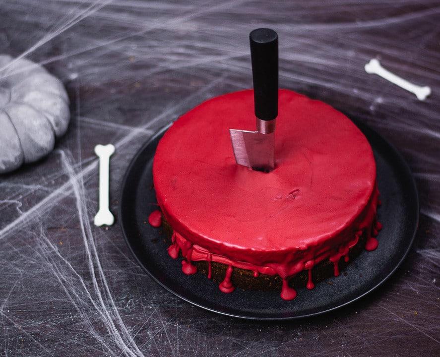 Ein blutiger Kuchen an dem an der Seite die rote Schokolade runter tropft. Die Schokolade sieht aus wie Blut
