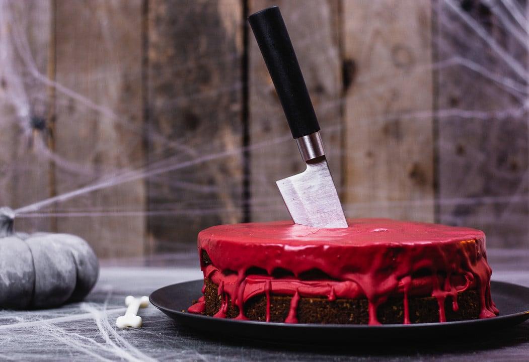 Ein blutiger Kuchen mit einem Messer das in der Kuchenmitte steckt