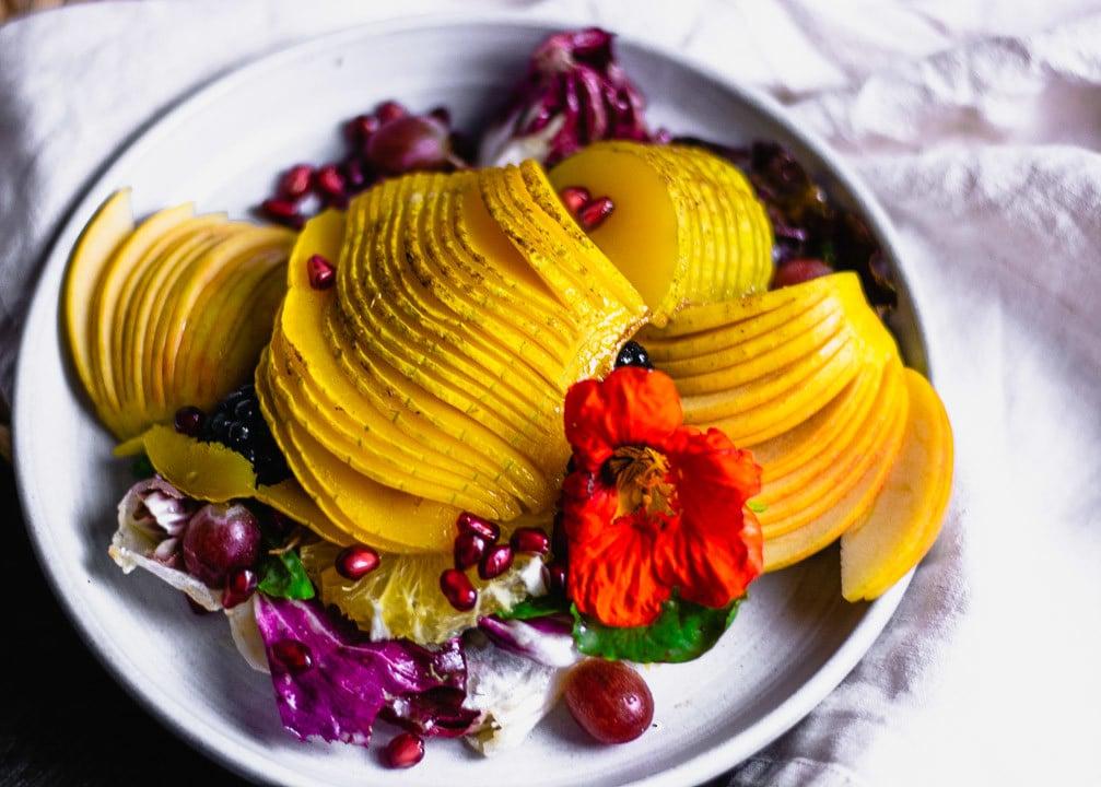 Ein bunter Herbstsalat auf einem Teller mit Blume