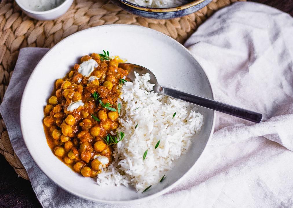 Ein Kichererbsen Curry in einer weißen Schale mit einem Löffel