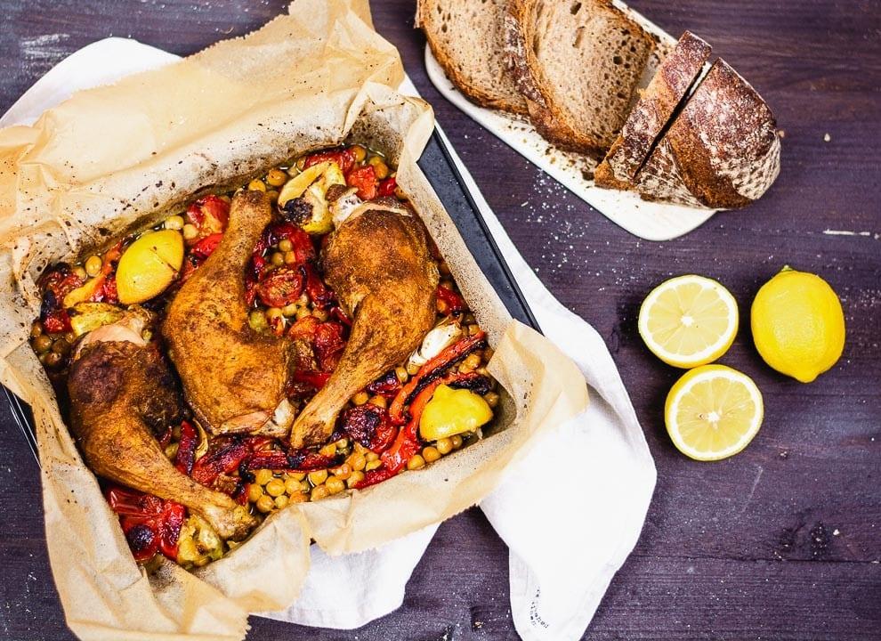 Eine Auflaufform mit Orientalische Hähnchenkeulen und Zitrone, Kartoffel, Kichererbsen und Paprika