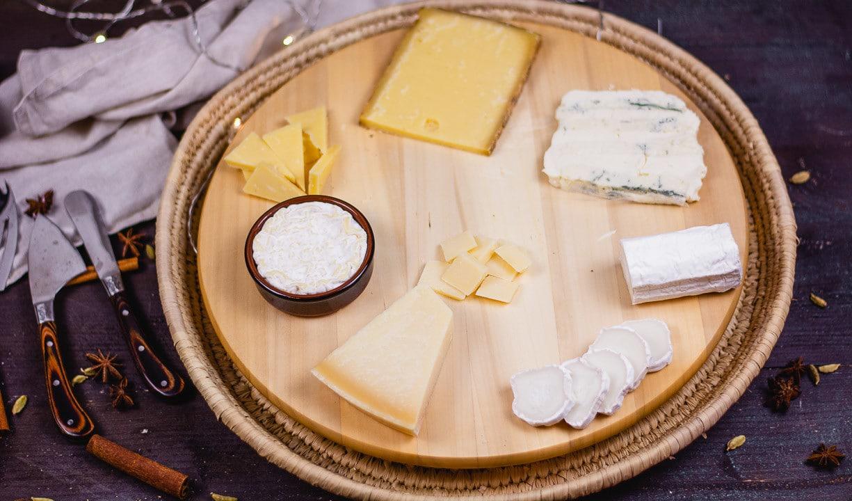 Fünf verschiedene Käse, Bergkäse, Pecorino, Gorgonzola, Ziegenkäserolle und Brie, auf einem runden Holzbrett