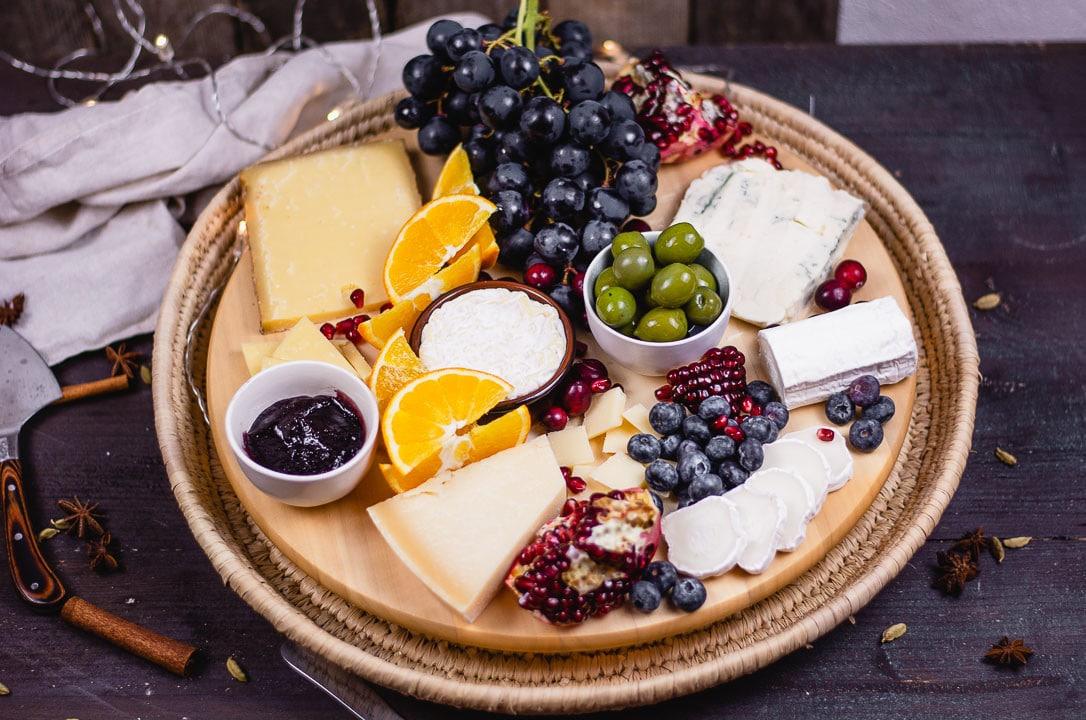 Weihnachtliche Käseplatte wird serviert. Das bunte Obst bildet einen hübschen Kontrast zu den hellen Käsen.